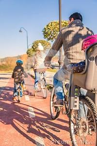 famiglia-con-i-bambini-che-guidano-le-biciclette-nella-natura-49573769